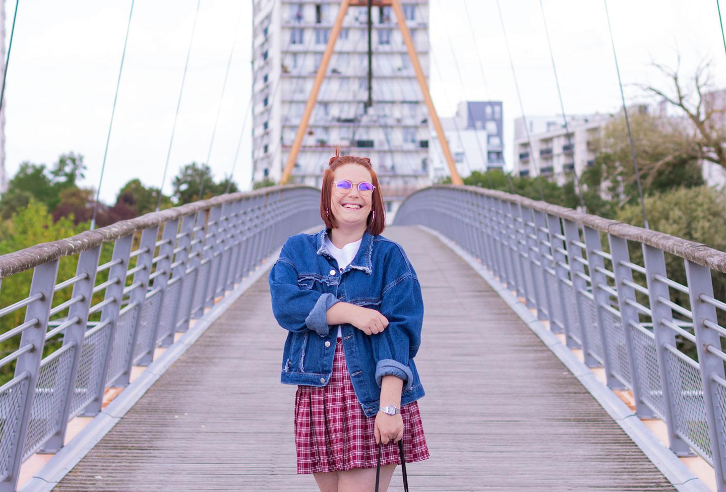 Veste en jean loose à franges et jupe bordeaux écolière, pour un look vintage au milieu d'un pont suspendu, avec le sourire