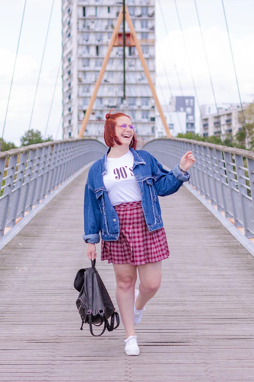Look écolière vintage, au milieu d'un pont avec un sourire béat, un sac à dos dans une main