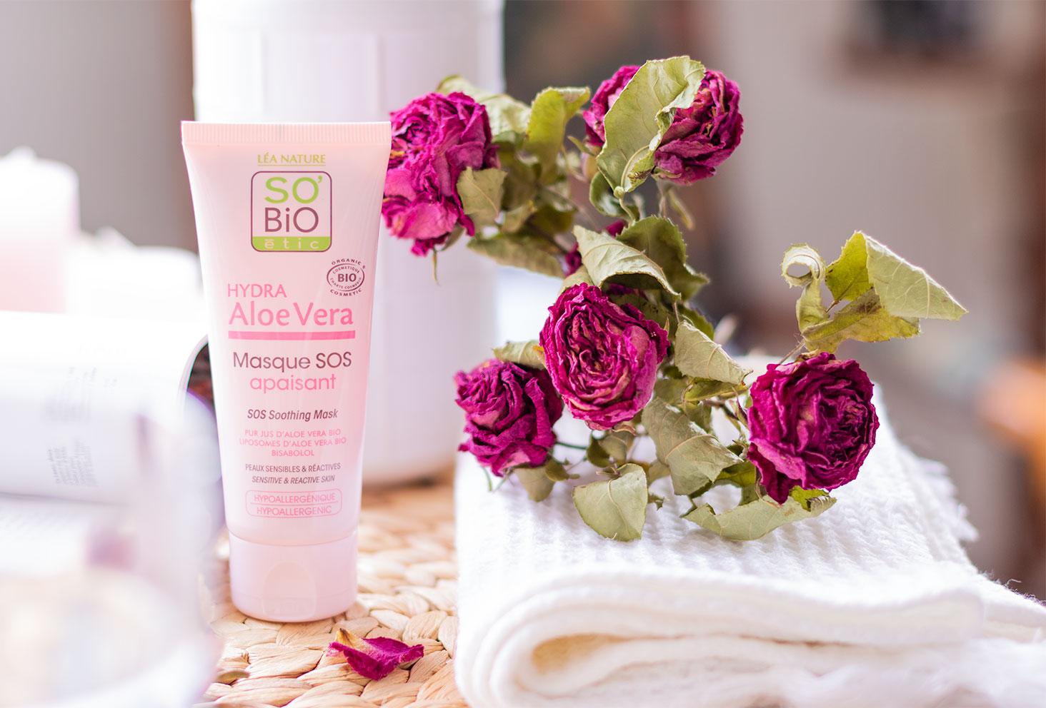 Le masque apaisant Hydra Aloe Vera de SO'BiO étic sur un dessous en osier, debout à côté de rose séchées et d'une serviette blanche