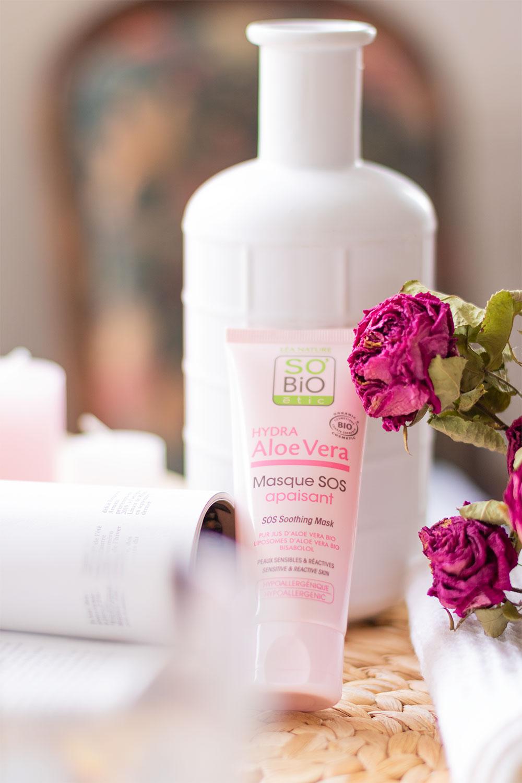 Le tube rose du masque SOS apaisant de SO'BiO étic appuyé le long d'une bouteille en verre blanche, sur un dessous en osier, caché derrière un magazine ouvert et des roses séchées