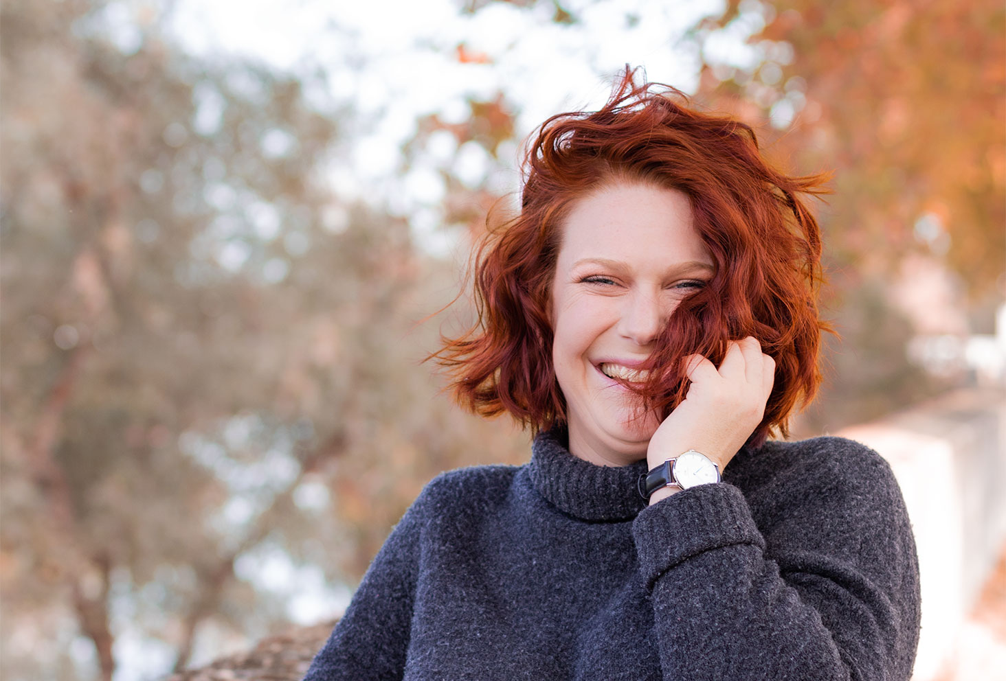 De face avec le sourire et les cheveux roux bouclés, la main dans les cheveux et en col roulé, zoom sur la montre DW noire portée