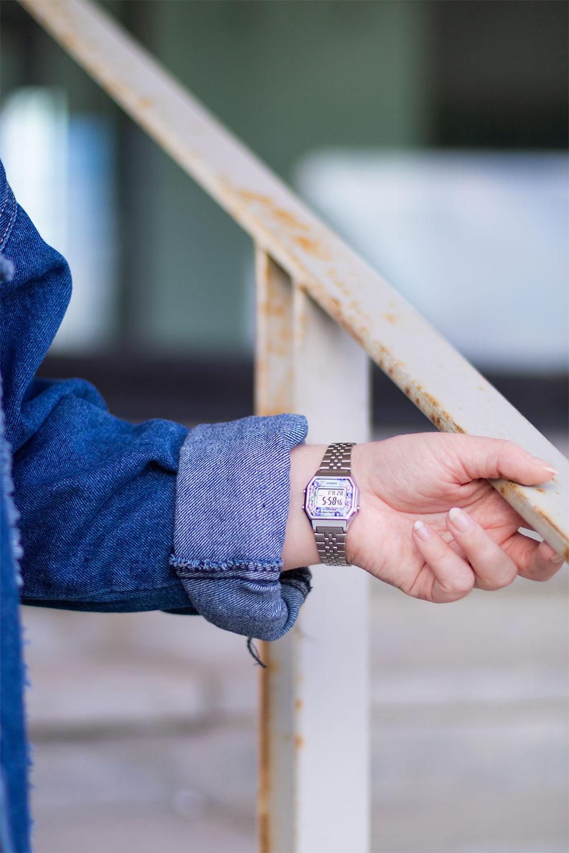 La main sur la rambarde, zoom sur une montre argentée vintage analogique de la marque Casio