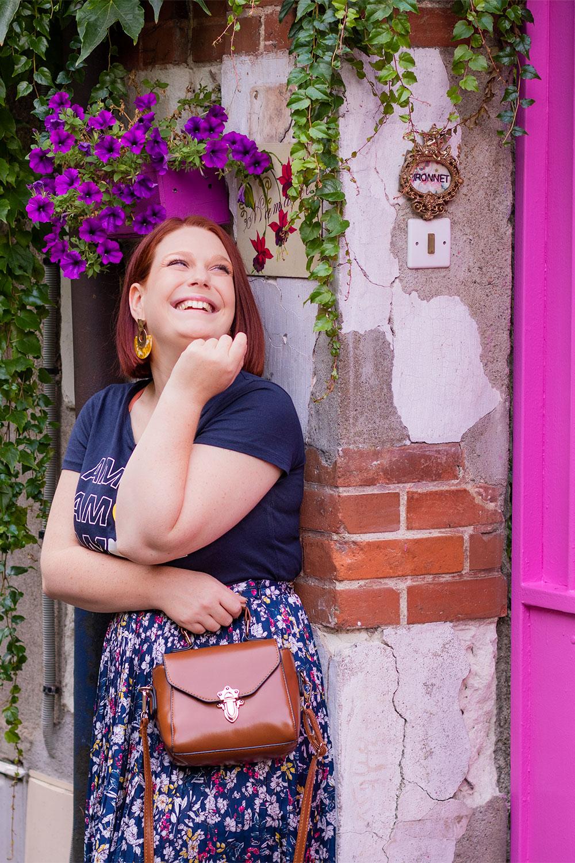 Le long d'un mur sous une jardinière colorée violette et à côté d'une porte rose, avec le sourire en jupe longue fleurie un sac marron dans la main