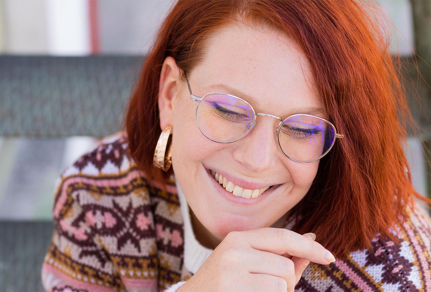 Portrait avec le sourire, les cheveux roux au soleil, assise dans des escaliers en métal vert