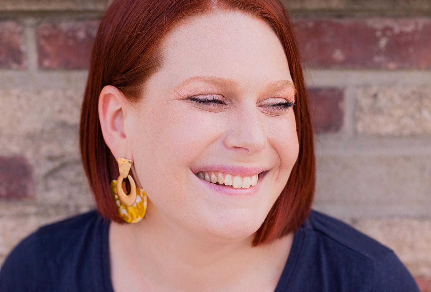 Photo portrait de face, avec le sourire, des boucles d'oreilles jaunes et dorées aux oreilles