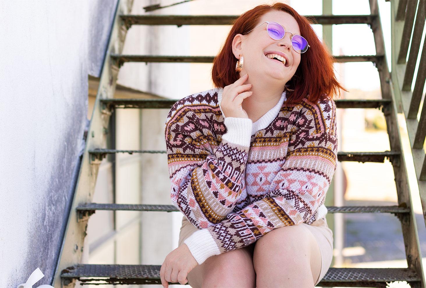 Assise avec le sourire dans des escaliers en métal verts, en pull oversize Bizzbee