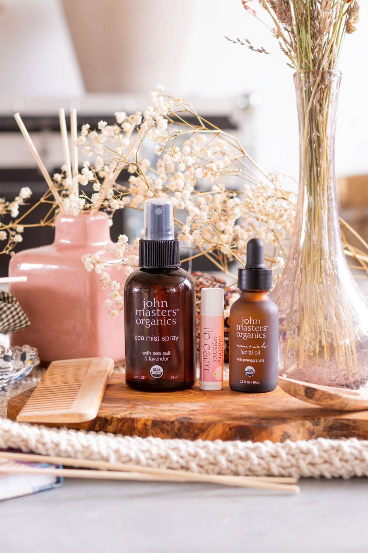 Les soins John Masters Organics sur une planche en bois au milieu de fleurs séchées, dans un décor de salle de bain vintage avant utilisation des produits