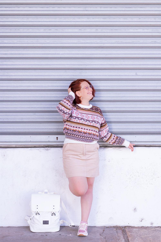 Appuyée sur un mur blanc, le long d'un rideau de fer, en pull d'hiver rose et beige et jupe en velours Bizzbee, le sac à dos blanc Gaston Luga posé aux pieds