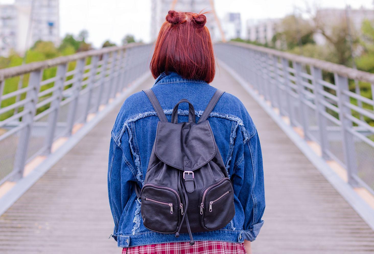 De dos au milieu d'un pont, en veste en jean, un sac à dos noir sur le dos et des petits chignons sur le haut de la tête