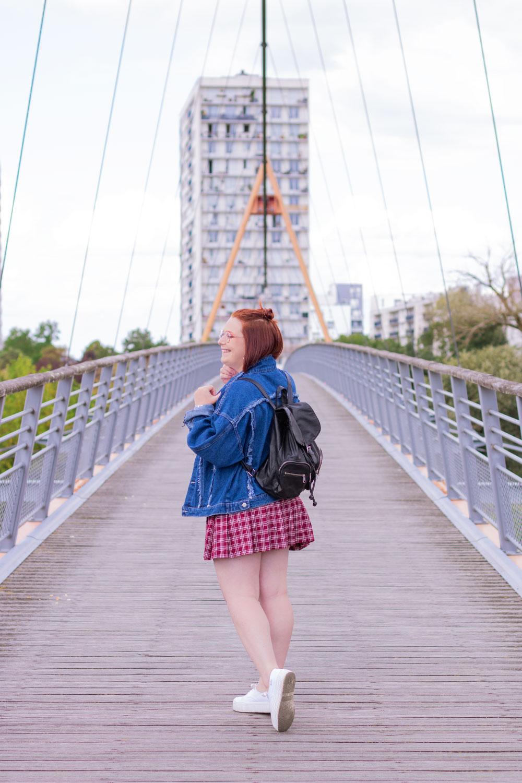 De dos en marchant, avec une veste oversize et un sac à dos noir sur le dos, au milieu d'un pont de fils