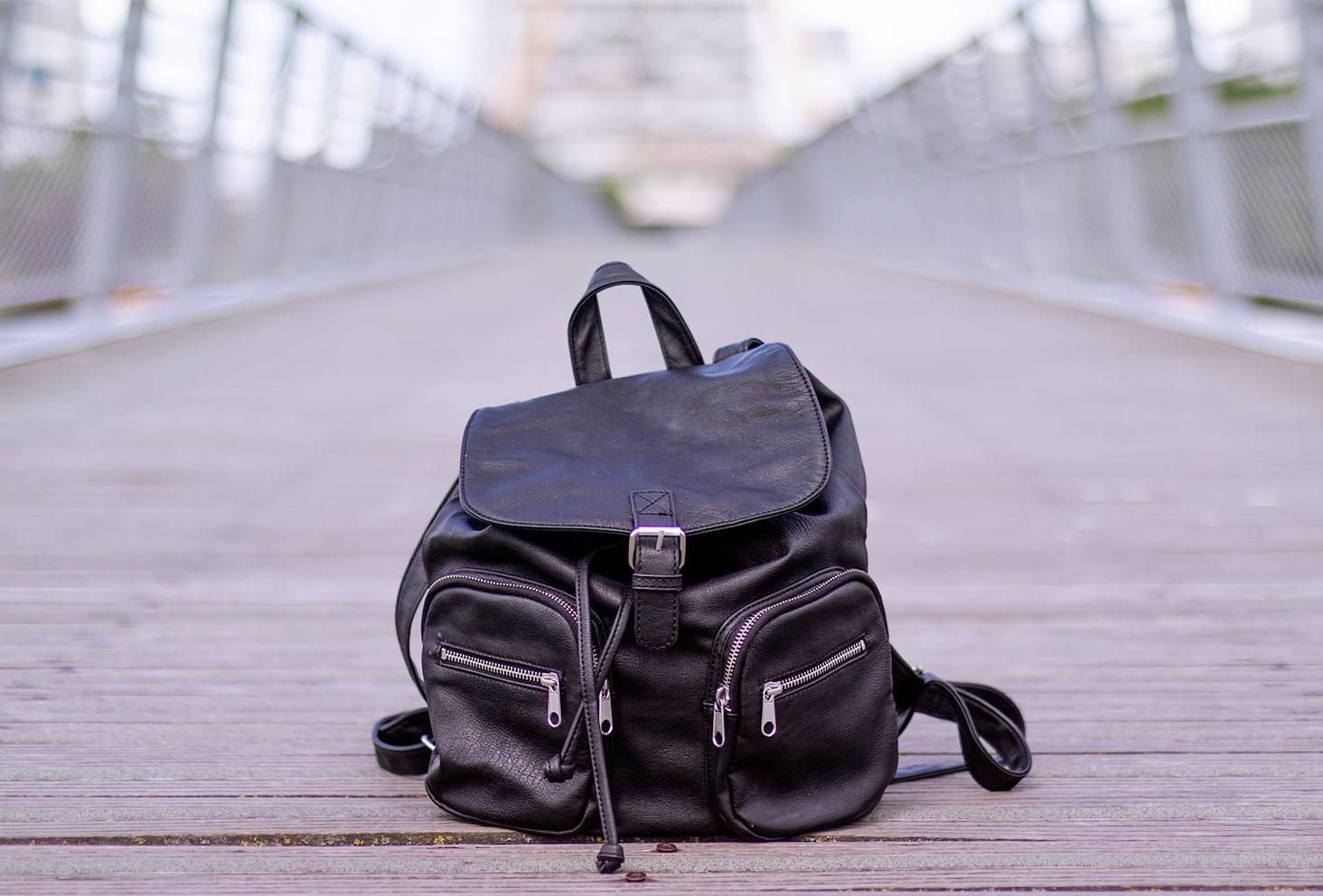 Un sac à dos noir en simili cuir posé sur un sol en bois, au milieu d'un pont suspendu