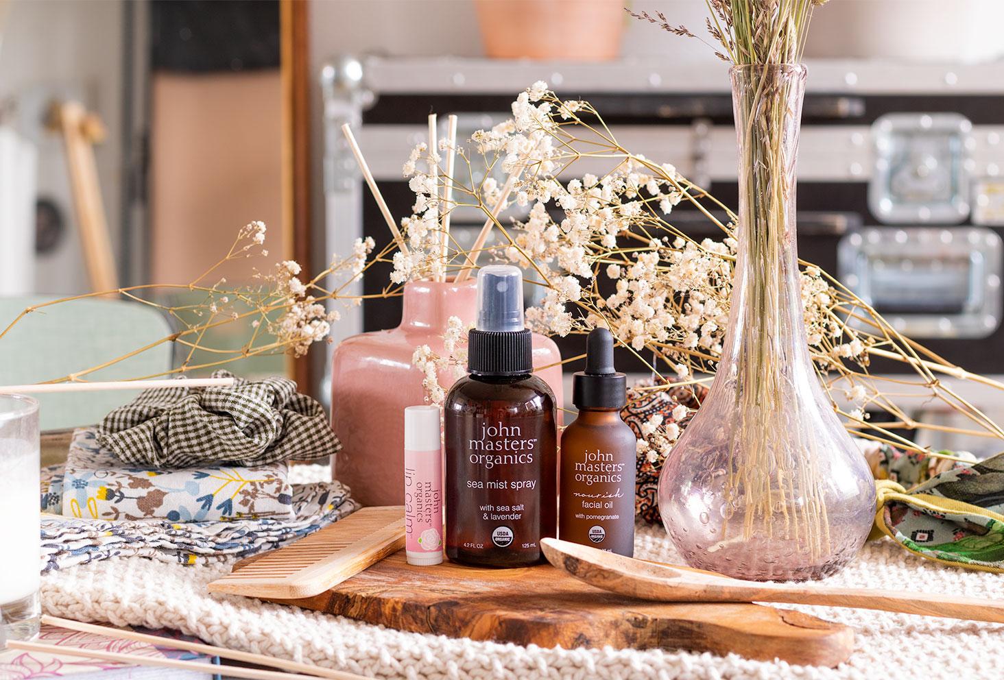 Les soins John Masters Organics sur une planche en bois au milieu de fleurs séchées, de déco vintage et d'ustensiles de salle de bain