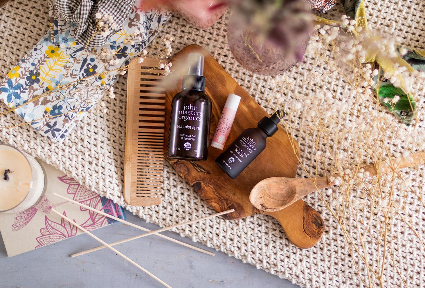 Les soins de John Masters Organics de haut, allongé sur une planche en bois, au milieu d'un décor de salle de bain vintage