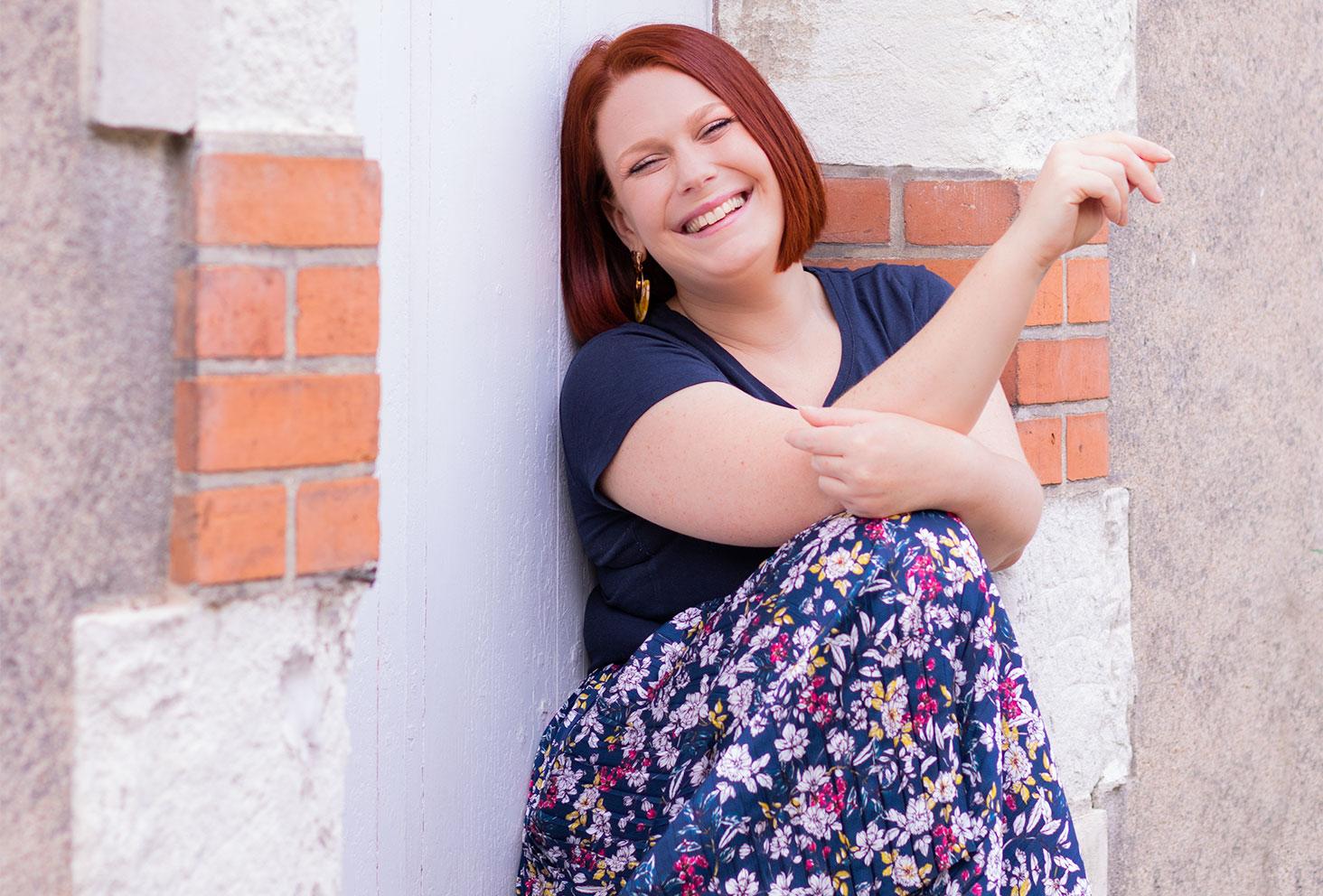 Assise sur le rebord d'une fenêtre avec le sourire, en longue jupe fleurie bleue
