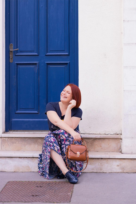 Assise sur les marches d'une porte d'entrée bleue, avec le sourire un petit sac marron dans la main, en derbies bleues et jupe longue fleurie