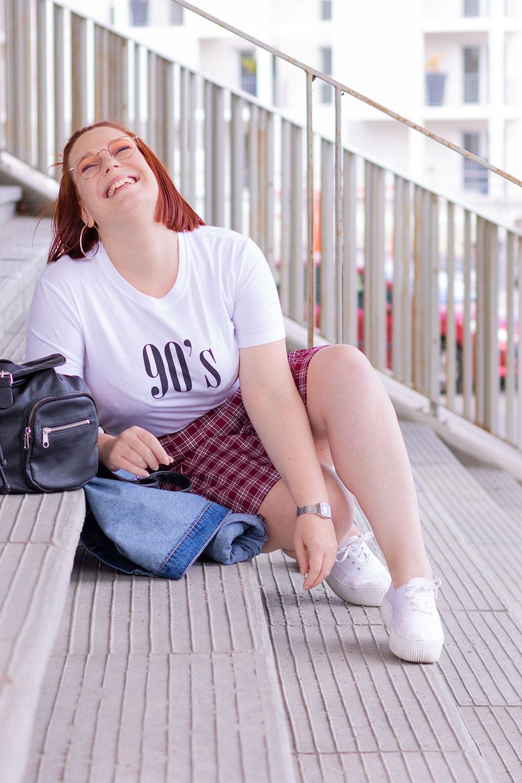 Assise dans des marches bétonnées de profil, avec le sourire dans un look street vintage 90's