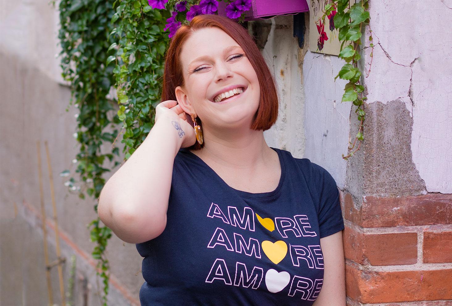 Le t-shirt bleu marine à motifs Amore de Naf-naf porté, avec le sourire et une main dans les cheveux, appuyée le long d'un mur près d'une jardinière fleurie violette