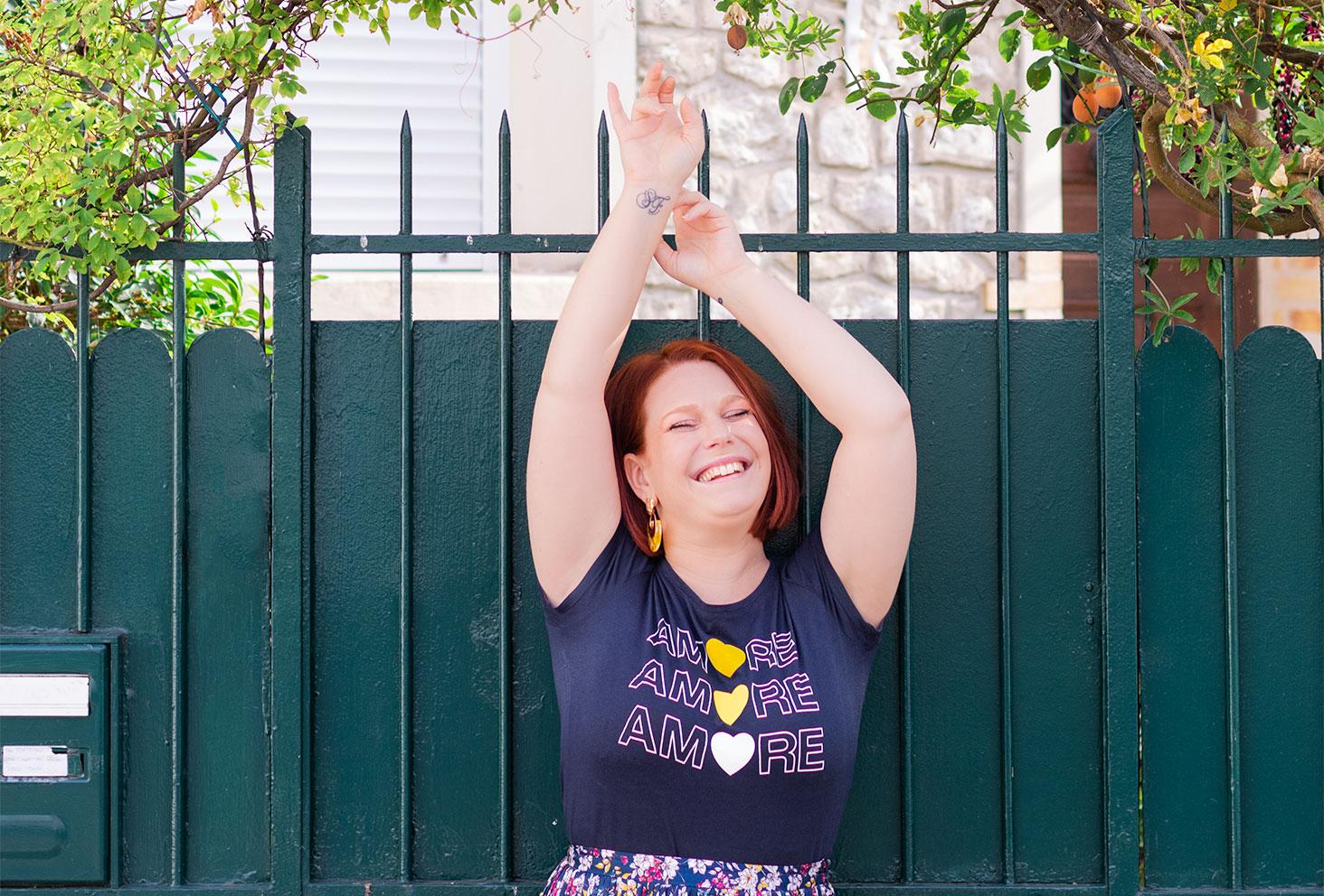 Le t-shirt au motif Amore bleu de Naf-naf porté pour la rentrée, les bras en l'air avec le sourire, le long d'un portail vert
