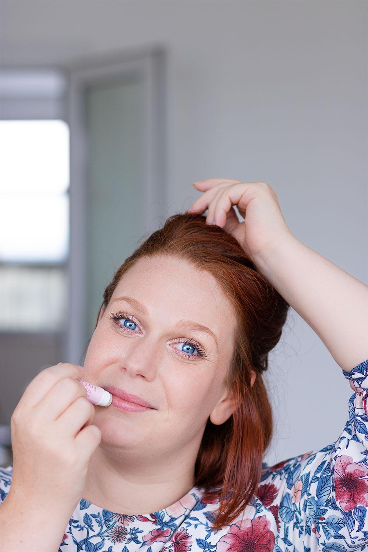 Utilisation du baume à lèvres hydratant de John Masters Organics avec le sourire, une main qui applique le baume et l'autre main dans les cheveux