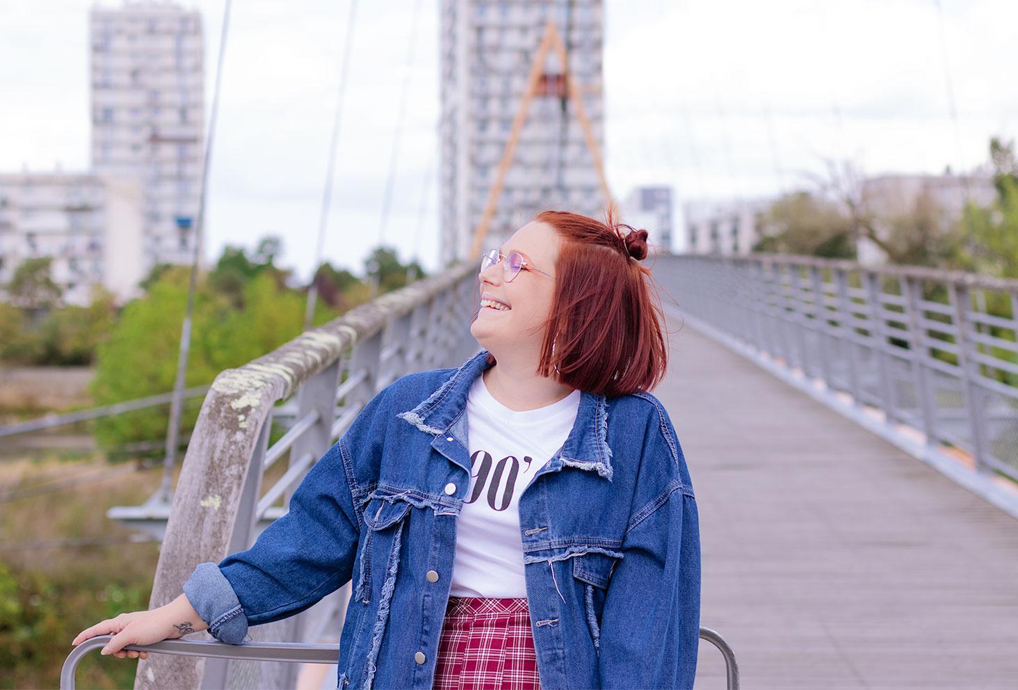 Avec le sourire de profil, zoom sur les chignons sur la tête et la veste en jean bleue oversize, appuyée le long d'une barrière en métal
