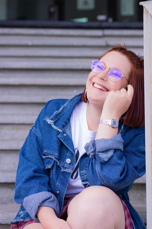 Assise dans les marches en béton, la tête posée contre la rambarde, en veste en jean oversize bleue et une montre argentée Casion vintage au poignet