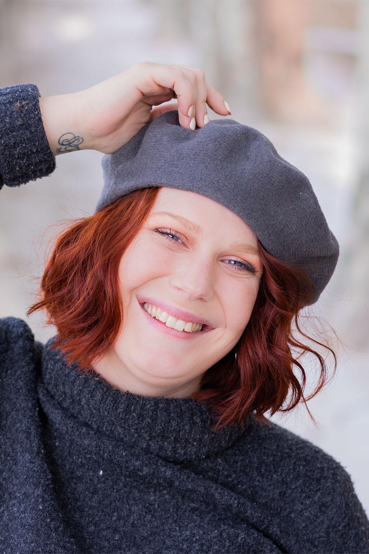 Zoom avec le sourire sur le béret gris foncé en laine portée, une main sur la tête et les cheveux roux bouclés