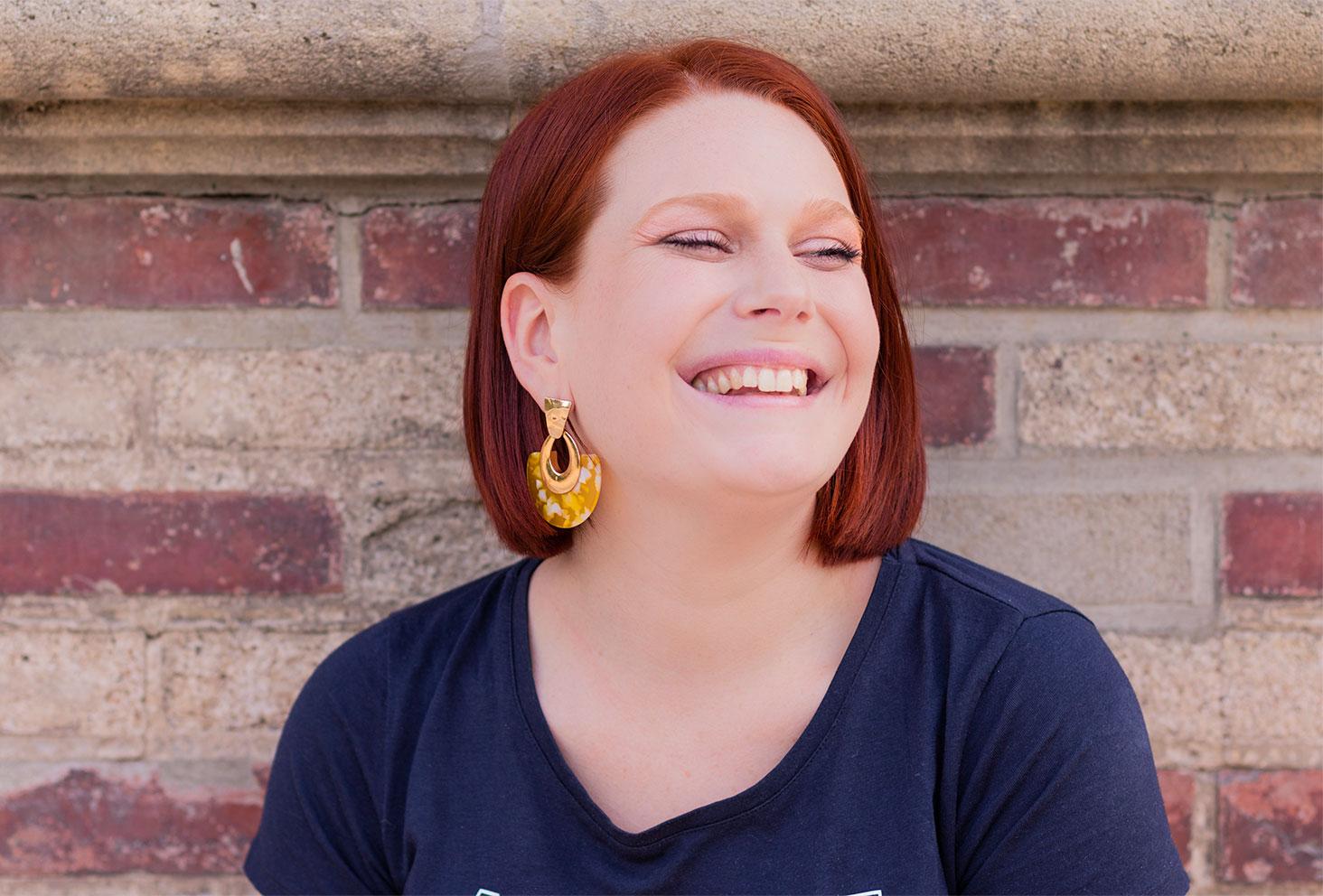 Zoom sur les boucles d'oreilles imposantes jaunes et dorées Springfield portées avec le sourire, les cheveux derrière l'oreille, en t-shirt bleu