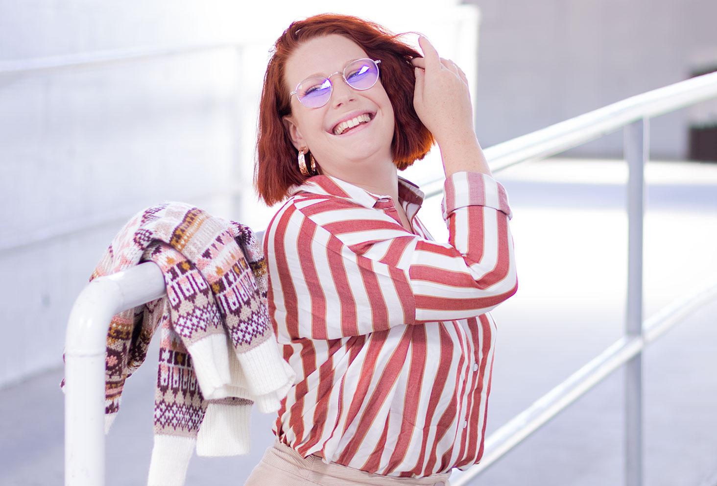 De profil, zoom sur la chemise oversize rayée blanche et rose de Bizzbee portée avec le sourire