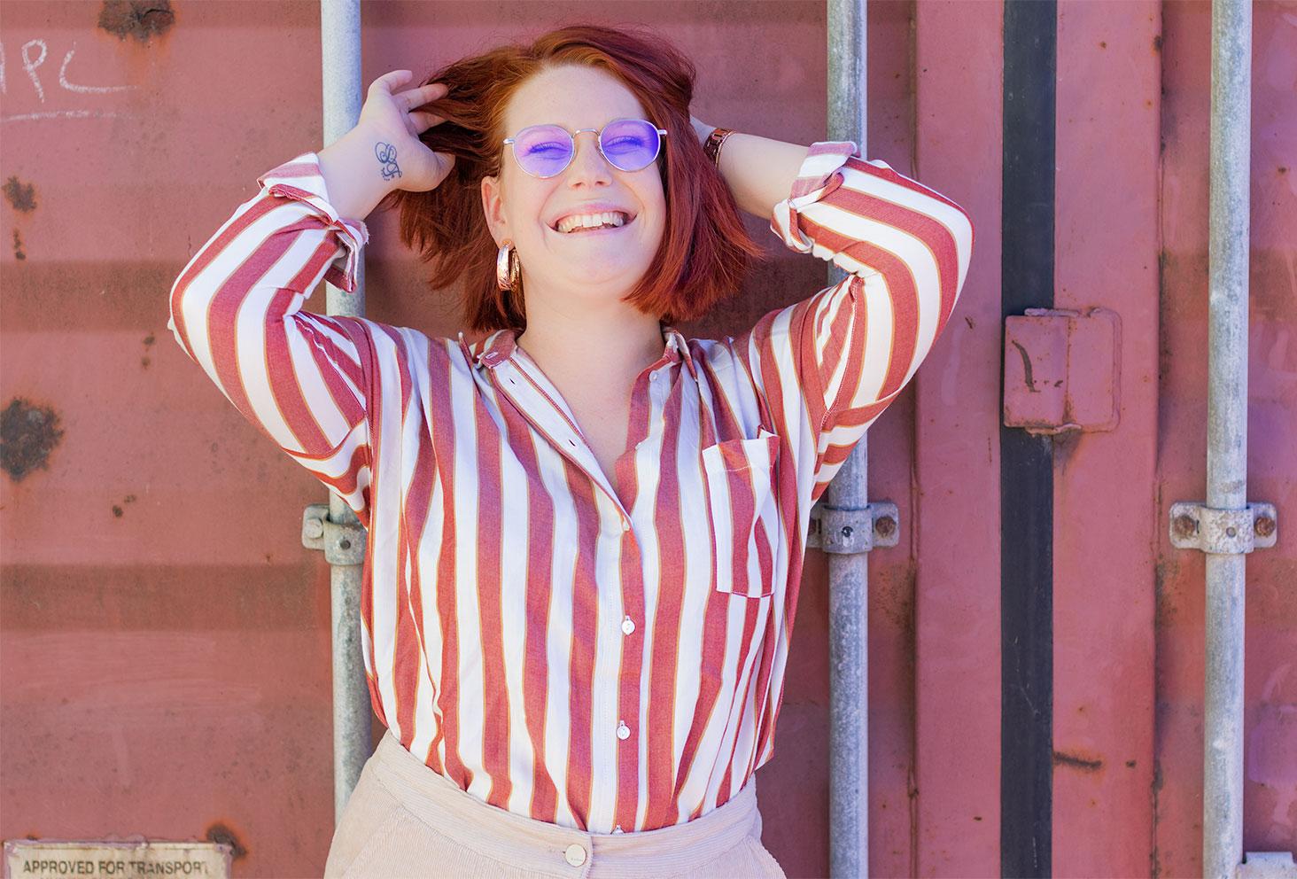 Avec le sourire le long d'un conteneur rose, zoom sur la chemise loose à rayures de la même couleur Bizzbee