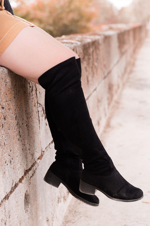 Zoom sur les cuissardes noires portées, assise sur un mur en pierre les jambes dans le vide