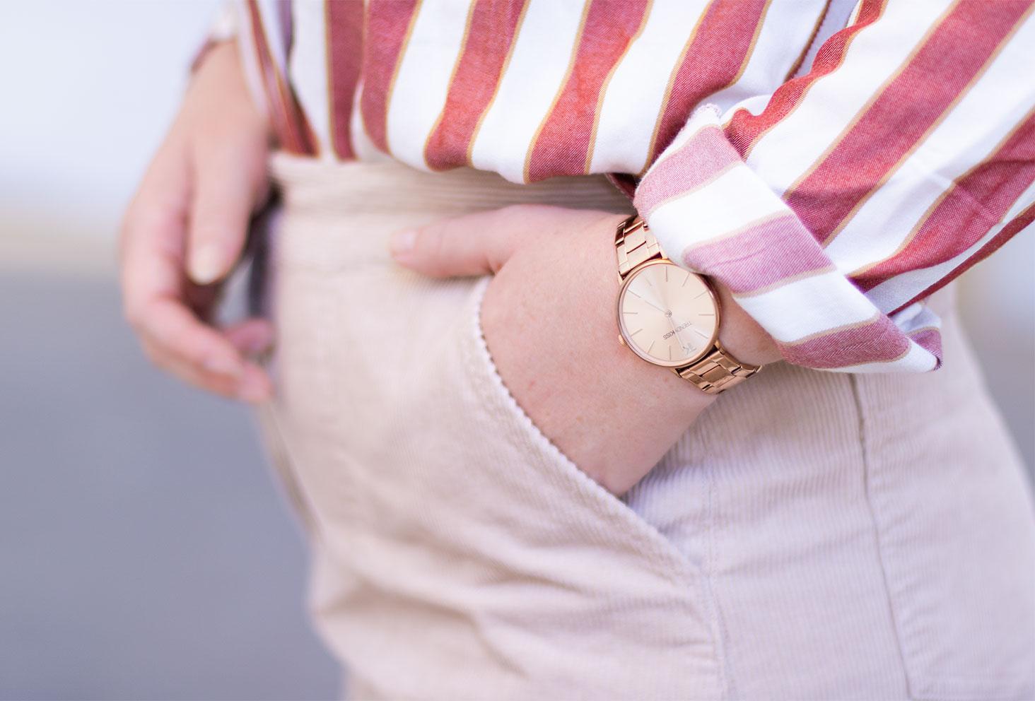 Zoom sur la montre dorée Trendy Kiss portée, la main dans la poche d'une jupe en velours beige