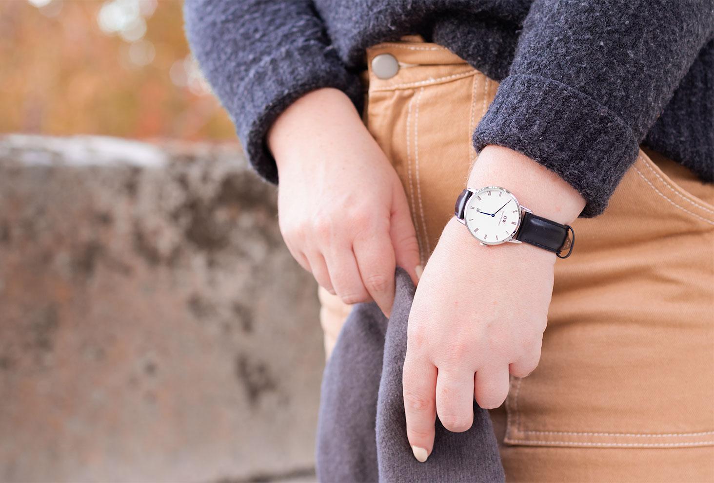 Zoom sur la montre noire Daniel Wellington portée, le béret gris tenu dans les mains devant une jupe en jean beige
