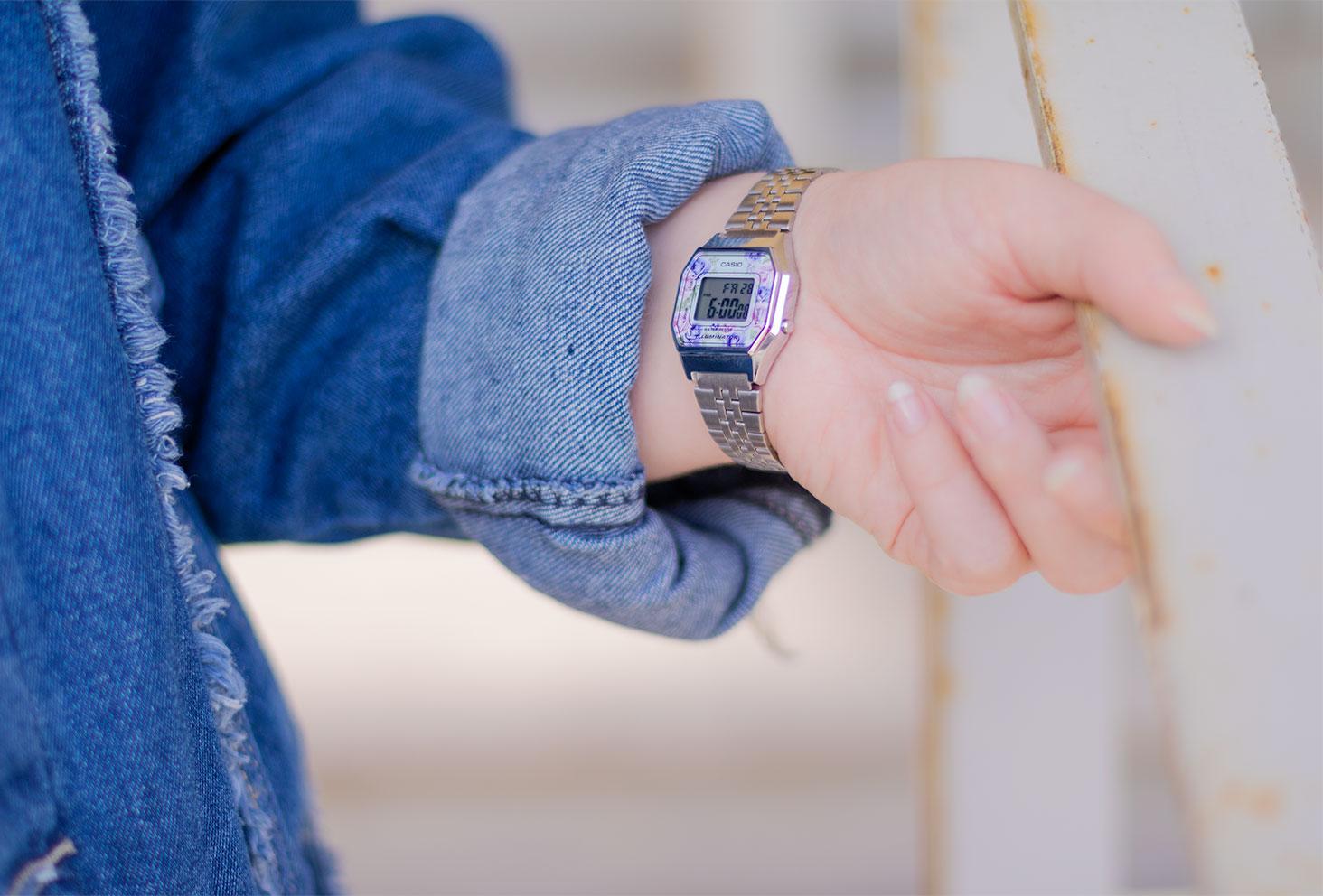 Zoom sur la montre Casio Vintage argentée au motifs floraux roses et violets portée, avec une veste en jean