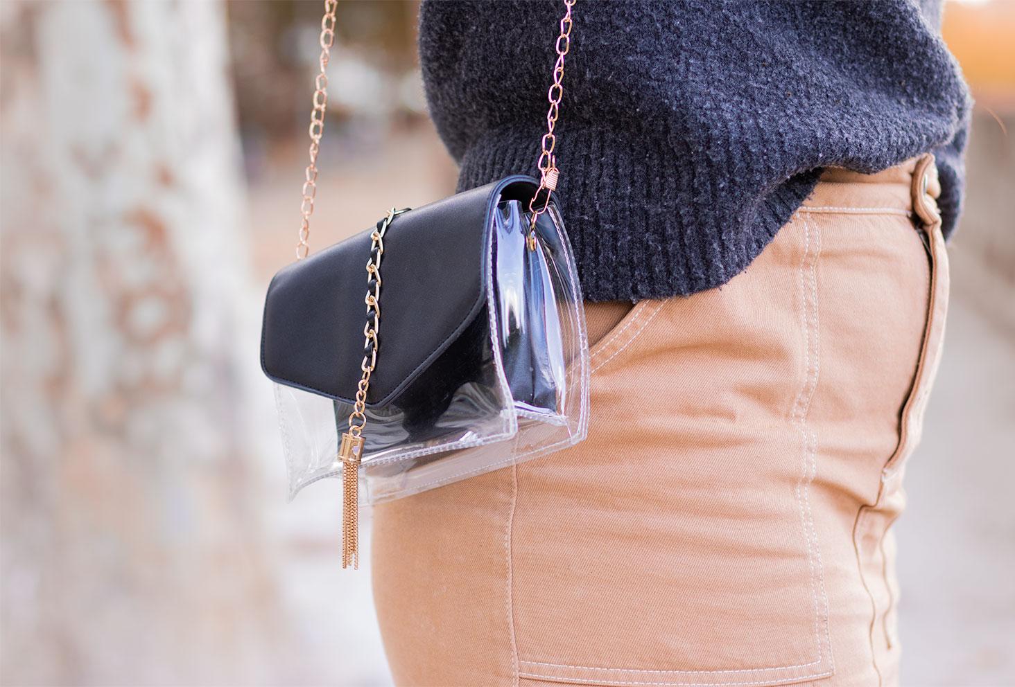 Zoom sur une petite pochette transparente et noire de SheIn portée avec une jupe en jean beige et un gros pull gris