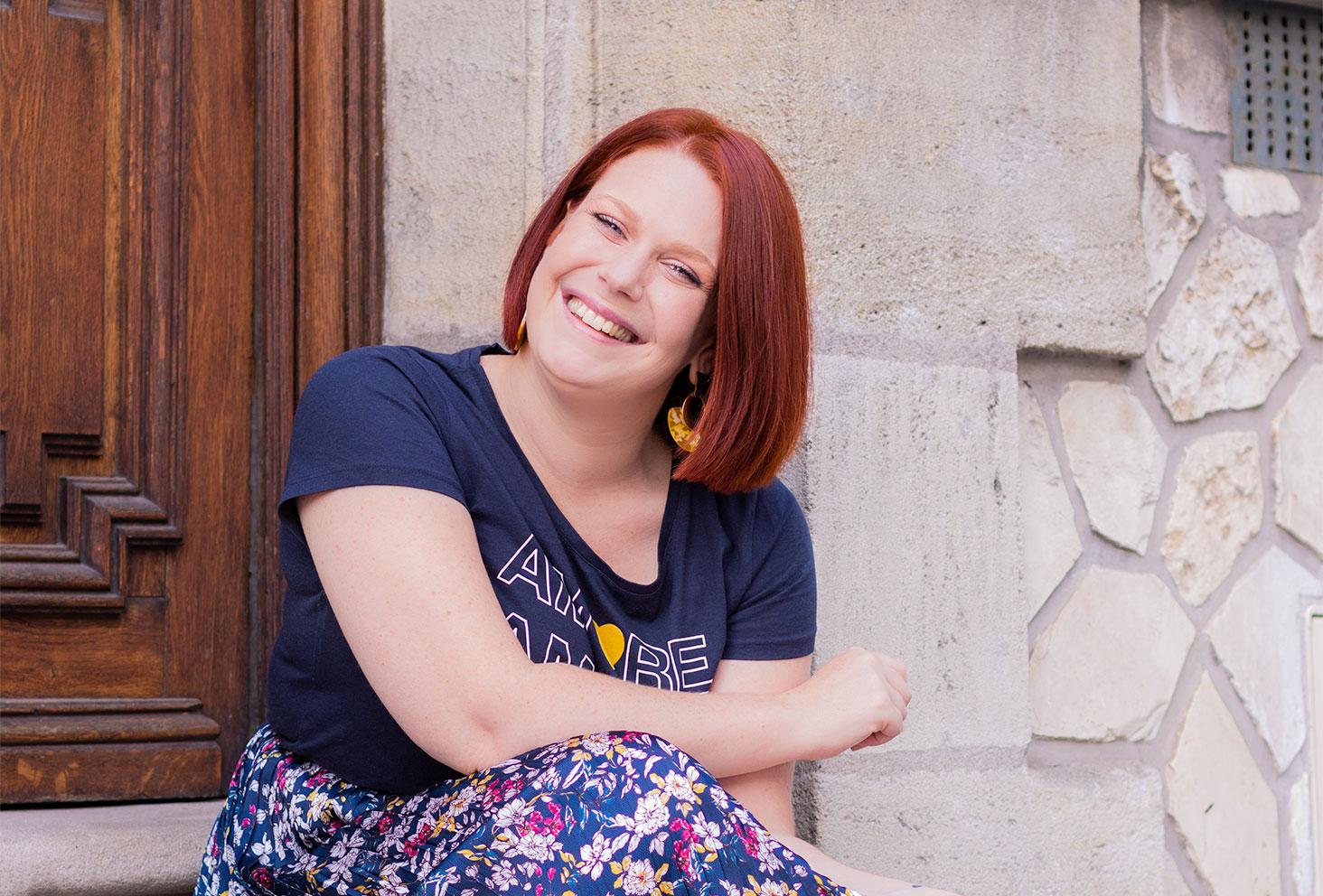 Assise le long d'un mur en pierre avec le sourire, légèrement de profil, en jupe fleurie et t-shirt bleu