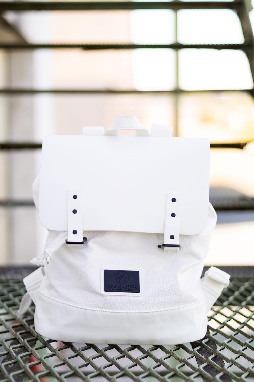 Zoom sur le sac à dos blanc de la marque Gaston Luga posé au milieu d'un escalier en métal vert