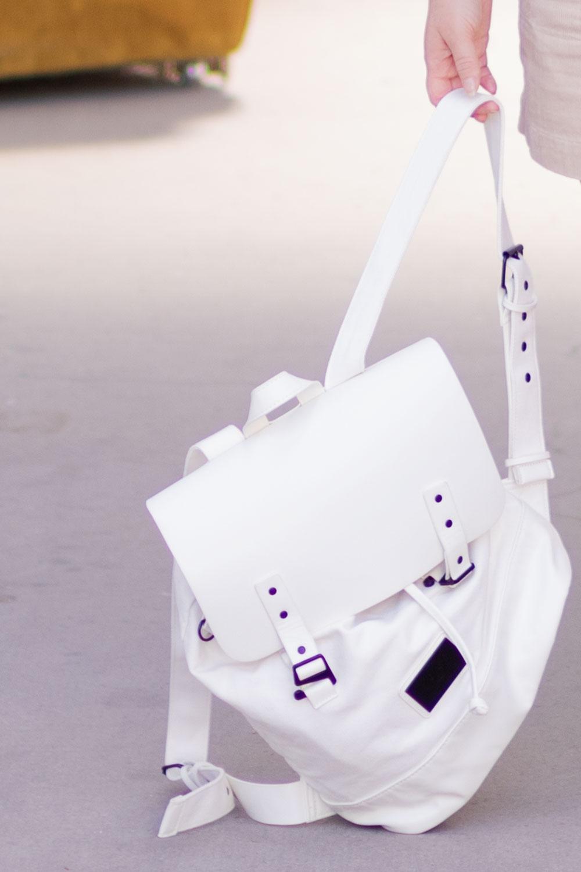 Zoom sur le sac à dos blanc Gaston Luga posé au sol mais tenu dans la main par une des bretelles