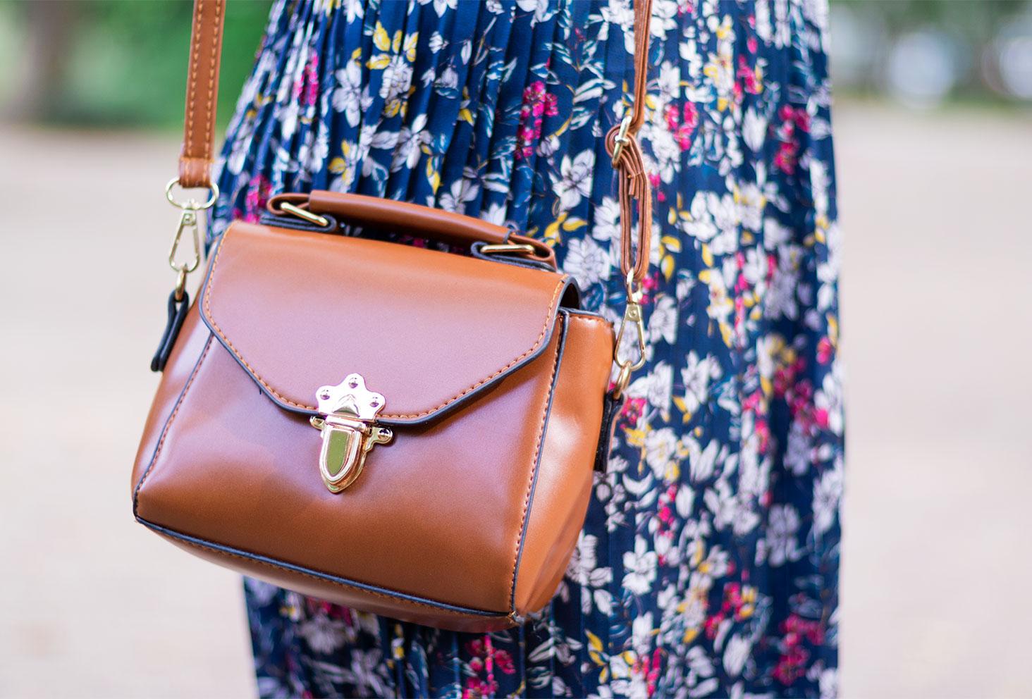 Zoom sur le sac camel Shein portée sur une jupe bleue à motifs floraux
