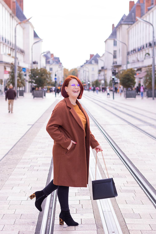 Au milieu de la rue Nationale à Tours, en look de working girl avec le sourire, des bottines à talons dans les pieds et un long manteau marron Bizzbee sur les épaules