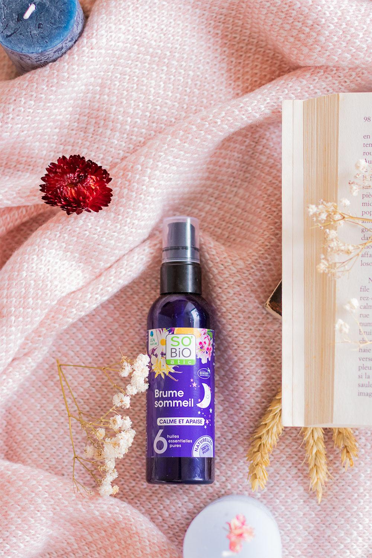 La brume sommeil aux huiles essentielles de SO'BiO étic allongée sur un plaid rose à côté d'un livre ouvert au milieu de fleurs séchées