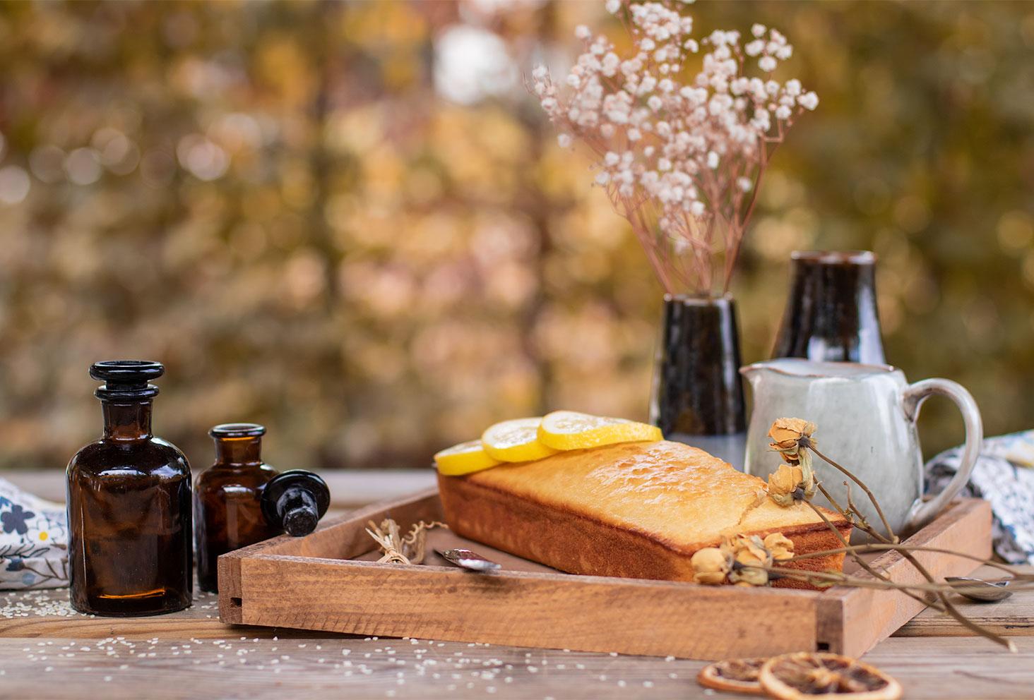 Un cake au citron moelleux avec des graines de sésame, sur un plateau en bois au milieu de fleurs séchées