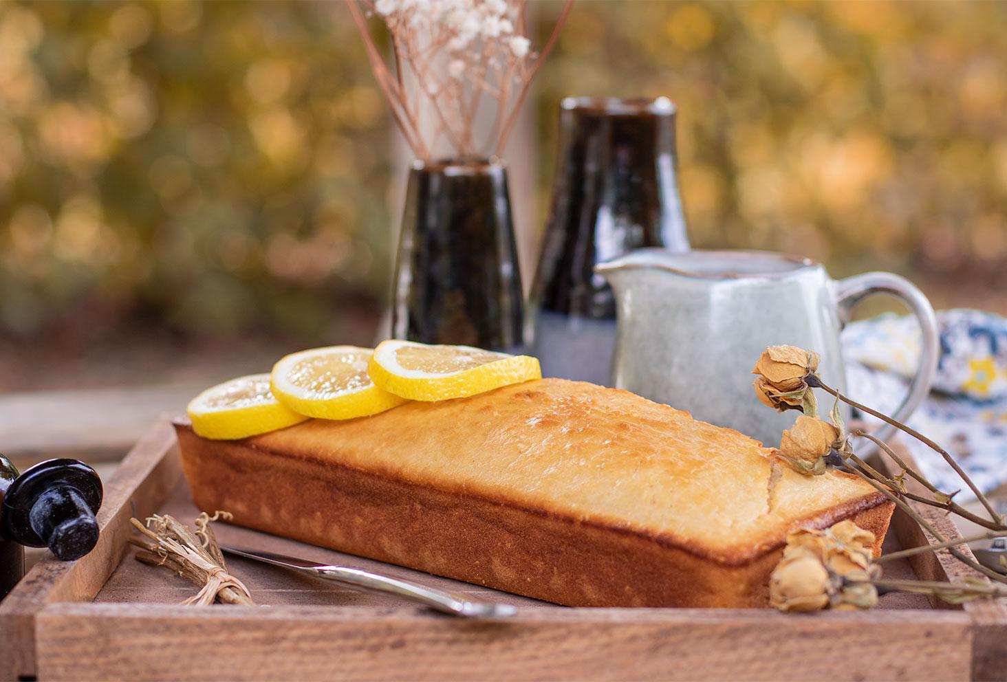 Zoom sur le cake au citron et graines de sésame au milieu de fleurs séchées et tranches de citron