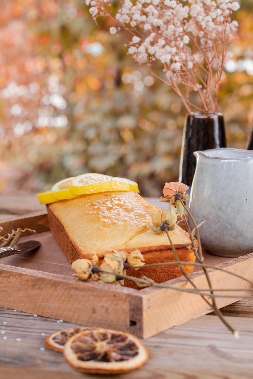 Un gâteau au citron pour le goûter facile et rapide, dans un plateau en bois au milieu de fleurs séchées