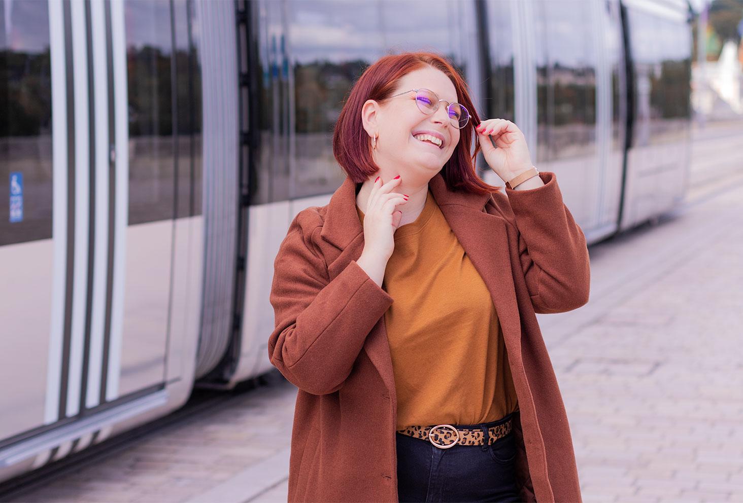 Devant le tramway en marche avec le sourire, une main dans le cou et l'autre dans les cheveux, un manteau marron long sur les épaules