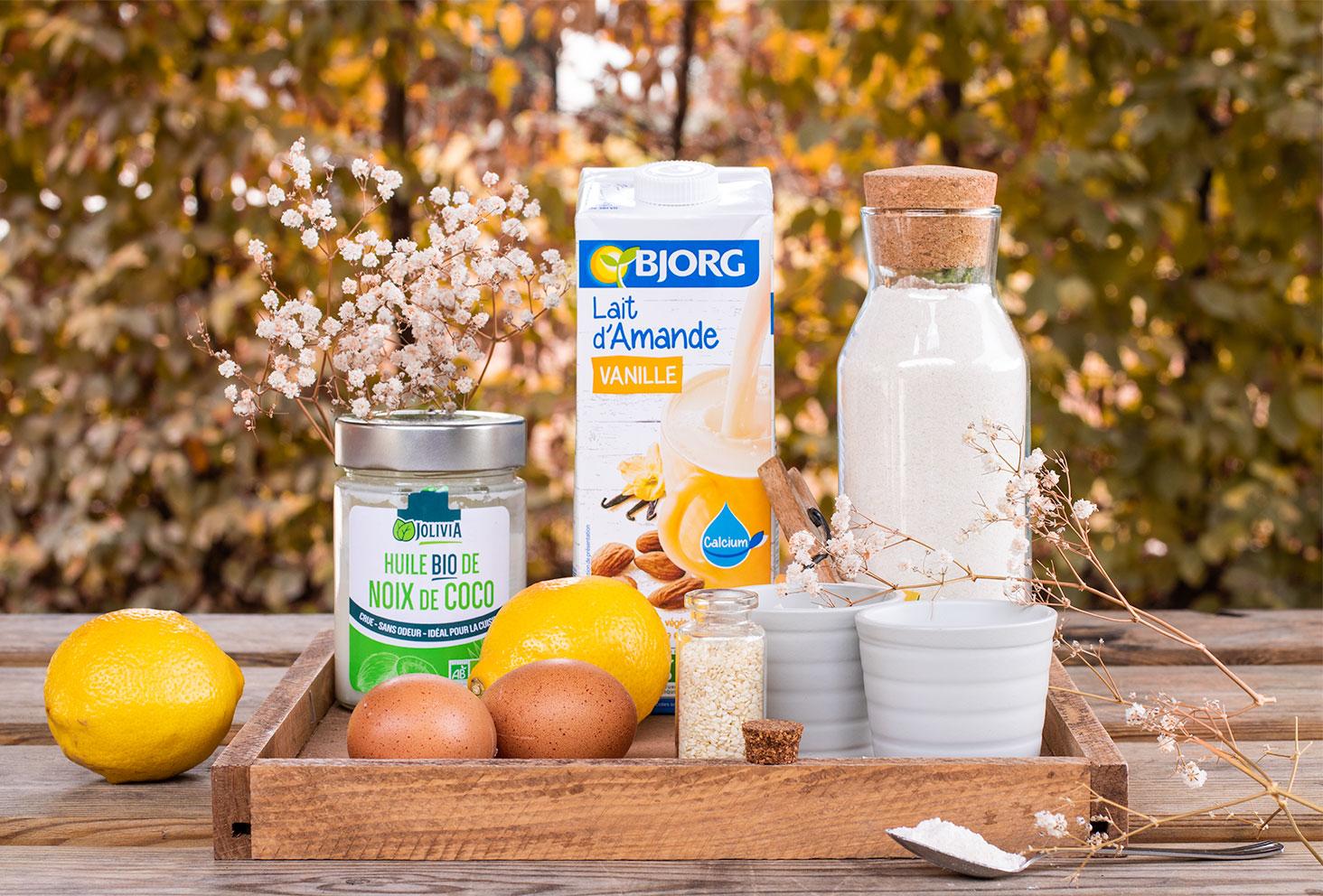 Les ingrédients nécessaires à la recette du cake au citron et graines de sésame, dans un plateau posé sur une table en bois