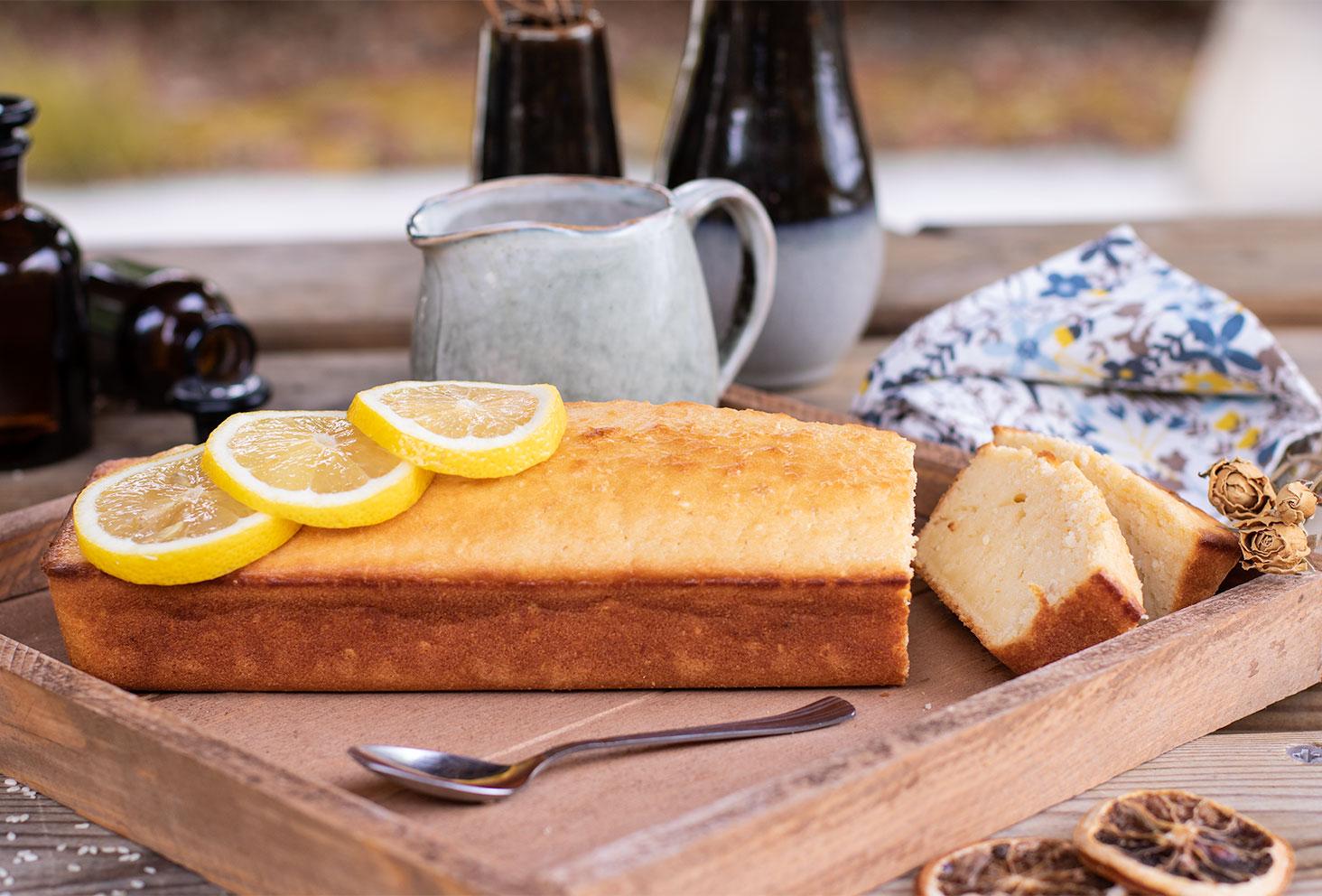Zoom sur un lemon cake aux graines de sésame coupé en tranche, posé sur un plateau en bois pour le goûter