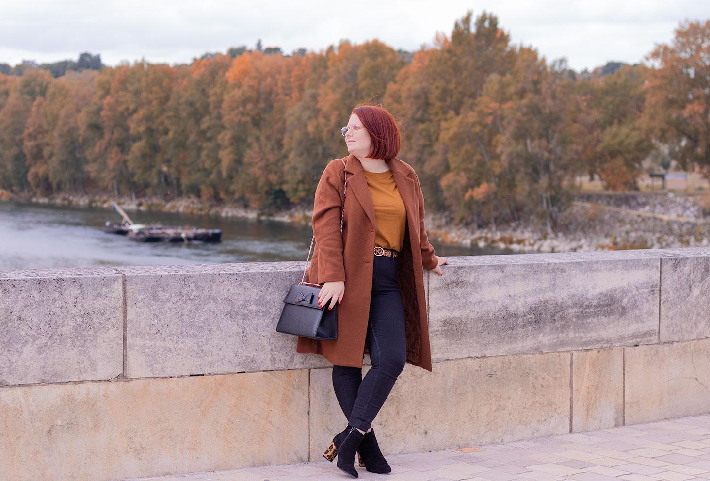 Appuyée le long du mur en pierre d'un pont au dessus de l'eau, en look de working girl