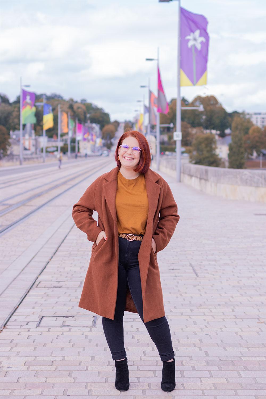 Sur un pont en pierre, les mains dans les poches d'un long manteau marron porté, avec le sourire pour fêter mes 28 ans