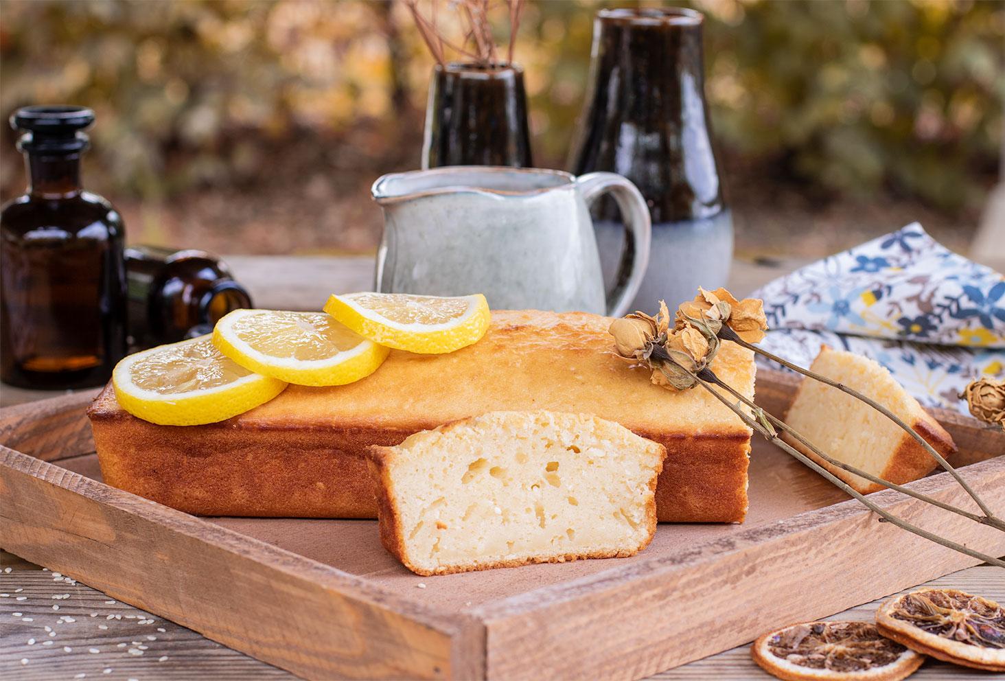 Une part de cake au citron coupée, posée le long du lemon cake, dans un plateau en bois au milieu d'une table de goûter