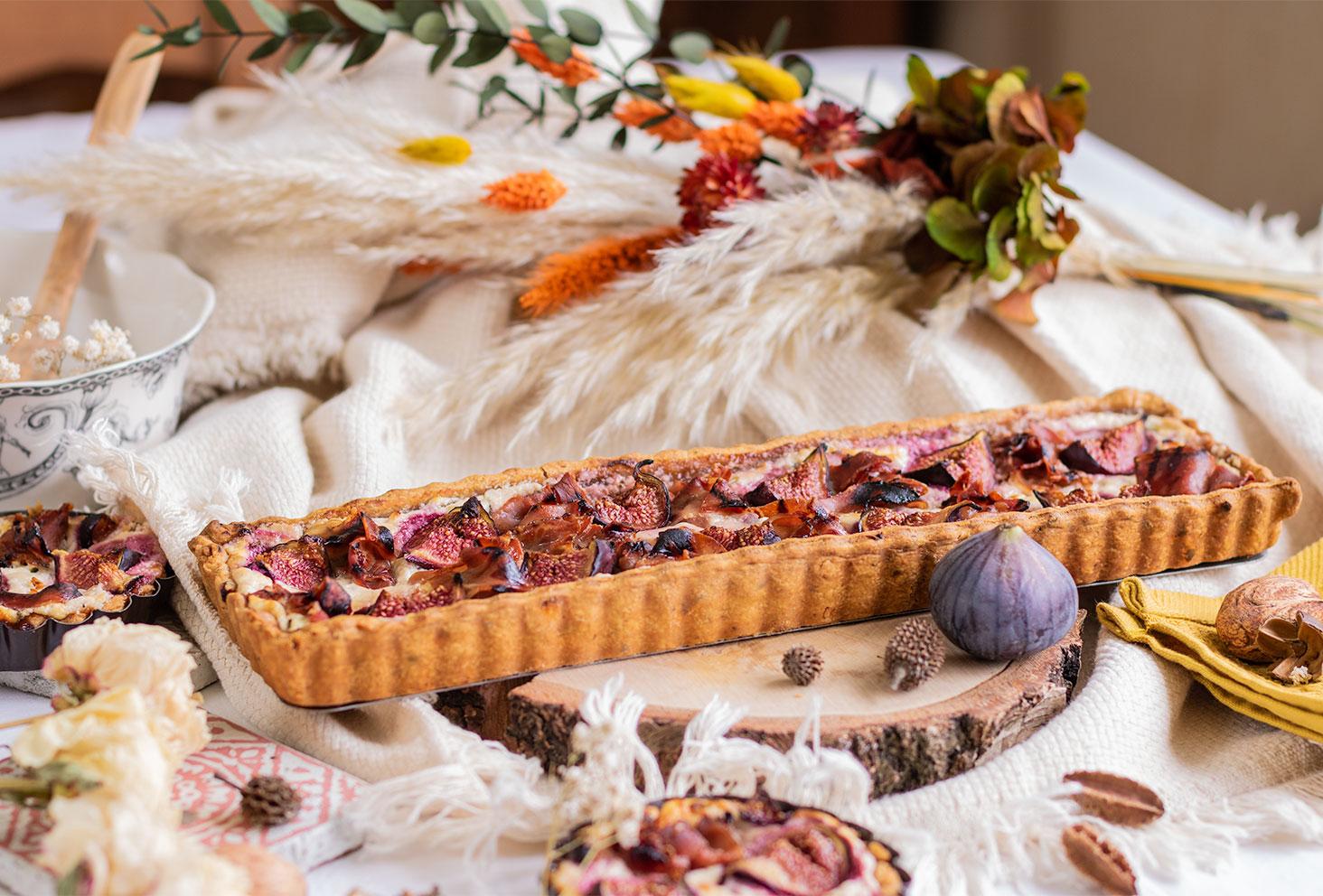 La tarte d'automne aux figues, chèvre frais et jambon, posée sur un rondin de bois au milieu d'un décor automnal
